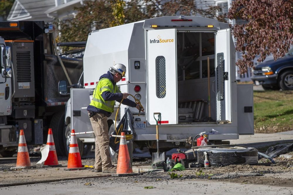 In late October, a utility worker hands a hose to another worker repairing gas lines underground on Salem Street in Lawrence. (Jesse Costa/WBUR)