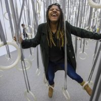 "At the ""William Forsythe: Choreographic Objects"" exhibit at the ICA, Niya Doyle enjoys herself climbing through the installation ""The Fact of Matter,"" where viewers are invited to traverse the space only using the dozens of rings suspended from the ceiling. (Jesse Costa/WBUR)"