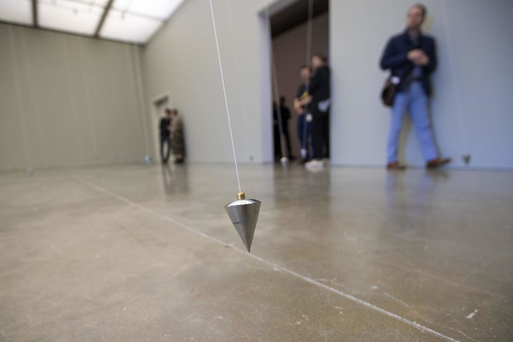 """One of the 80 swinging pendulums of """"In Nowhere and Everywhere at the Same Time, No. 3."""" (Jesse Costa/WBUR)"""