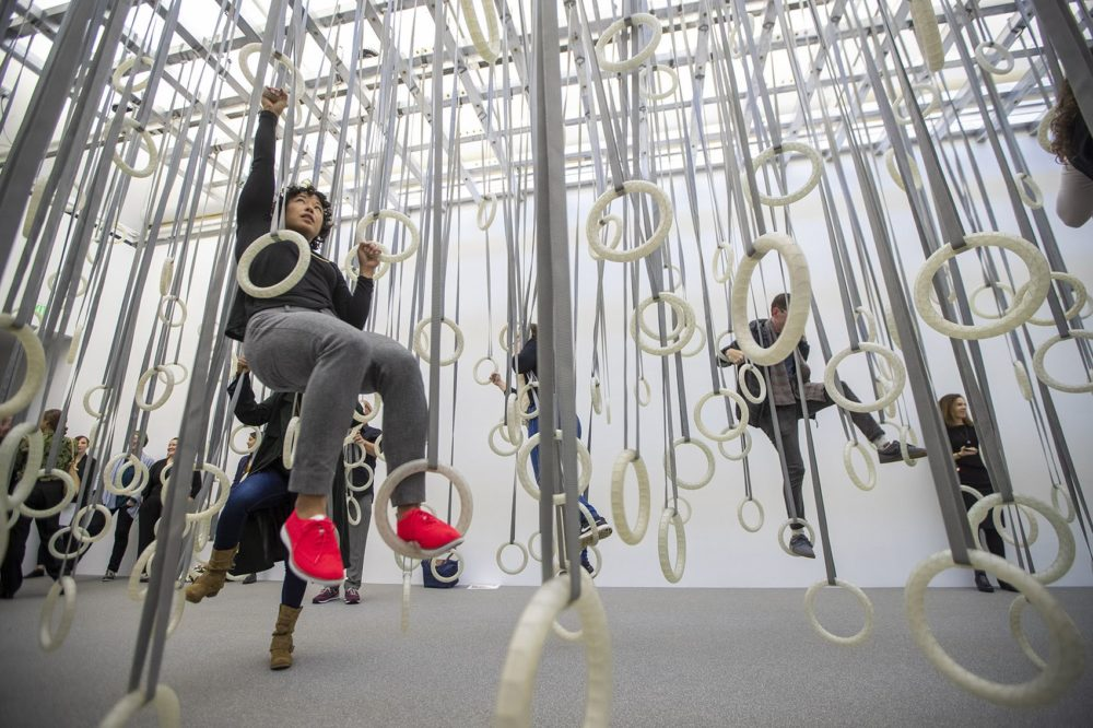 """ICA curator Ellen Tani climbs through the rings of """"In The Fact of Matter."""" (Jesse Costa/WBUR)"""
