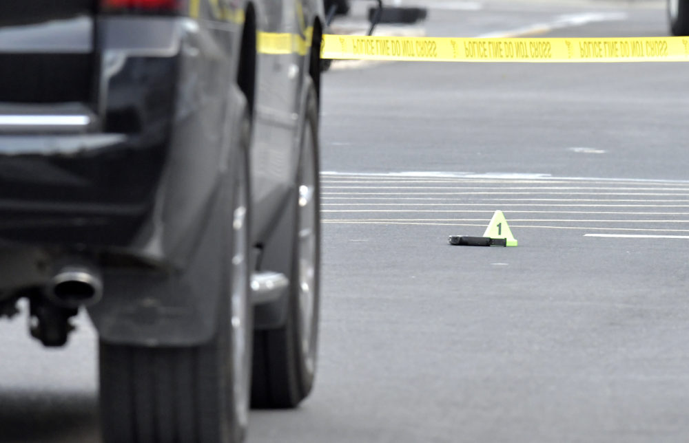 A suspect in a double homicide reportedly opened fire on a party after being asked to leave. Here, a gun lies on the ground next to an evidence marker outside of a Kroger Grocery in Jeffersontown, Ky., Wednesday, Oct. 24, 2018,. The shooting left two people dead, and the subject in custody. (Timothy D. Easley/AP)