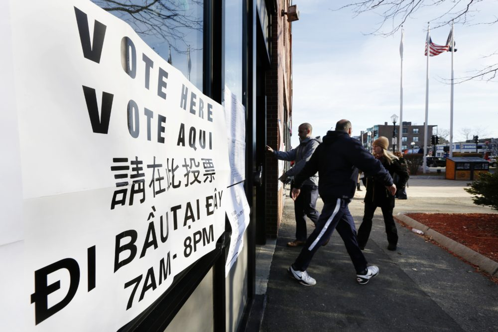 Voters arrive and depart at a polling station for Massachusetts' primary election in the East Boston neighborhood of Boston in 2016. Voting materials appear here in several languages. (Michael Dwyer/AP)