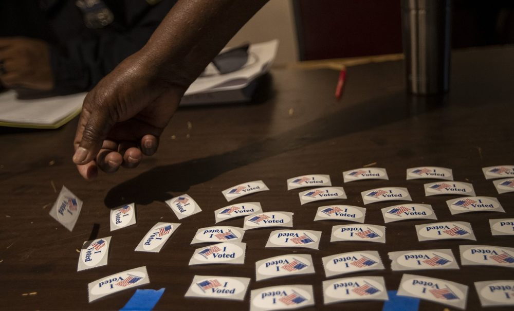 "An election worker at Morning Star Baptist Church lays down ""I Voted"" stickers on a table for voters to pick up after they have voted. (Jesse Costa/WBUR)"