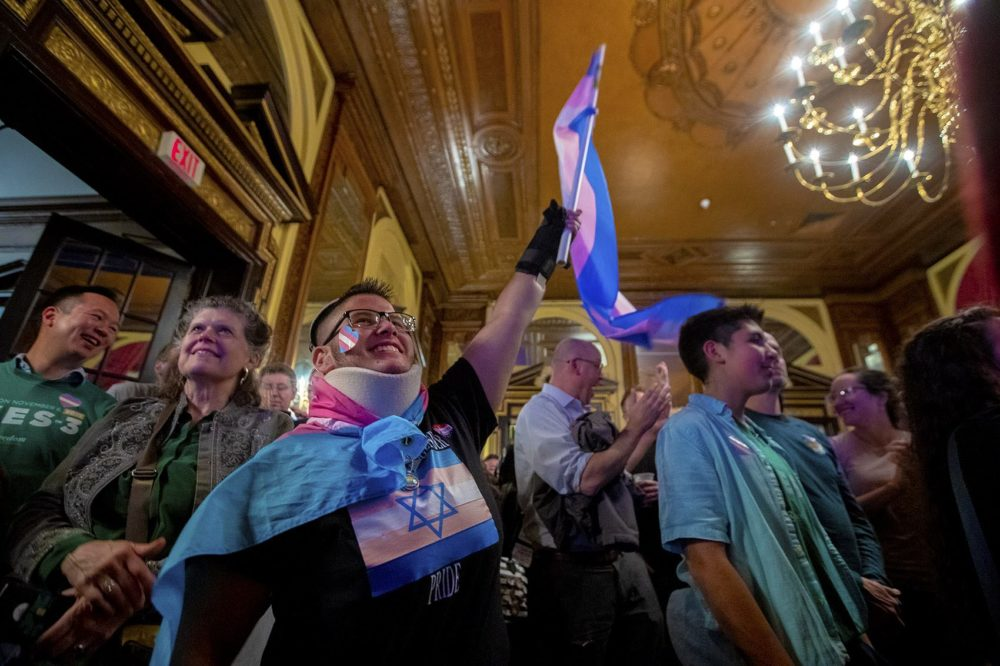 Mateo Cox waves a transgender flag excitedly as the room at the Fairmont Copley learns of the election day win. (Jesse Costa/WBUR)