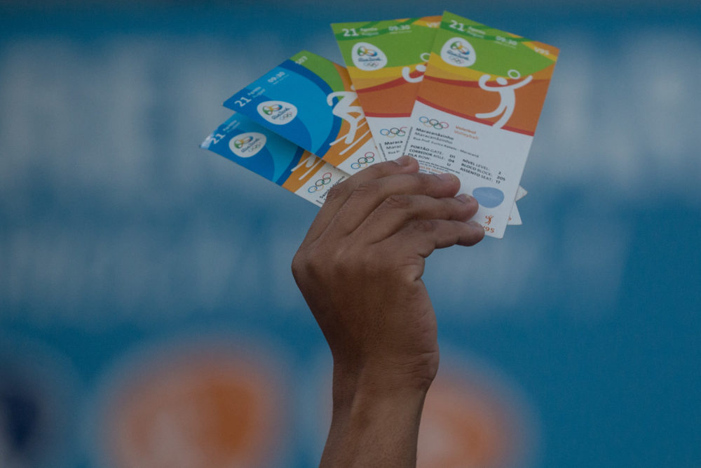 A man holds up tickets to sell or swap outside a venue at the Rio 2016 Olympic Games on Aug. 19, 2016 in Rio de Janeiro, Brazil. (Chris McGrath/Getty Images)