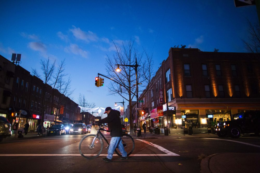 People walk on a local street past restaurants in Astoria in the Queens borough of New York. (Eduardo Munoz Alvarez/AFP/Getty Images)