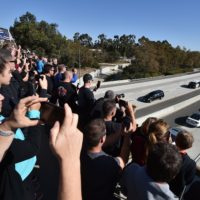 Firefighters, law enforcement and members of the public watch as the hearse carrying the body of Ventura County Sheriff's Sgt. Ron Helus, the first victim named in the mass shooting at a country bar in Thousand Oaks, Calif., is transported in a procession Nov. 8, 2018. (Robyn Beck/AFP/Getty Images)