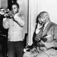 W.C. Handy (right) nods approval and chuckles as an eighth-grade pupil, Donell Callaway, 13, wails blues on his trumpet in New York City in 1954. (AP Photo)