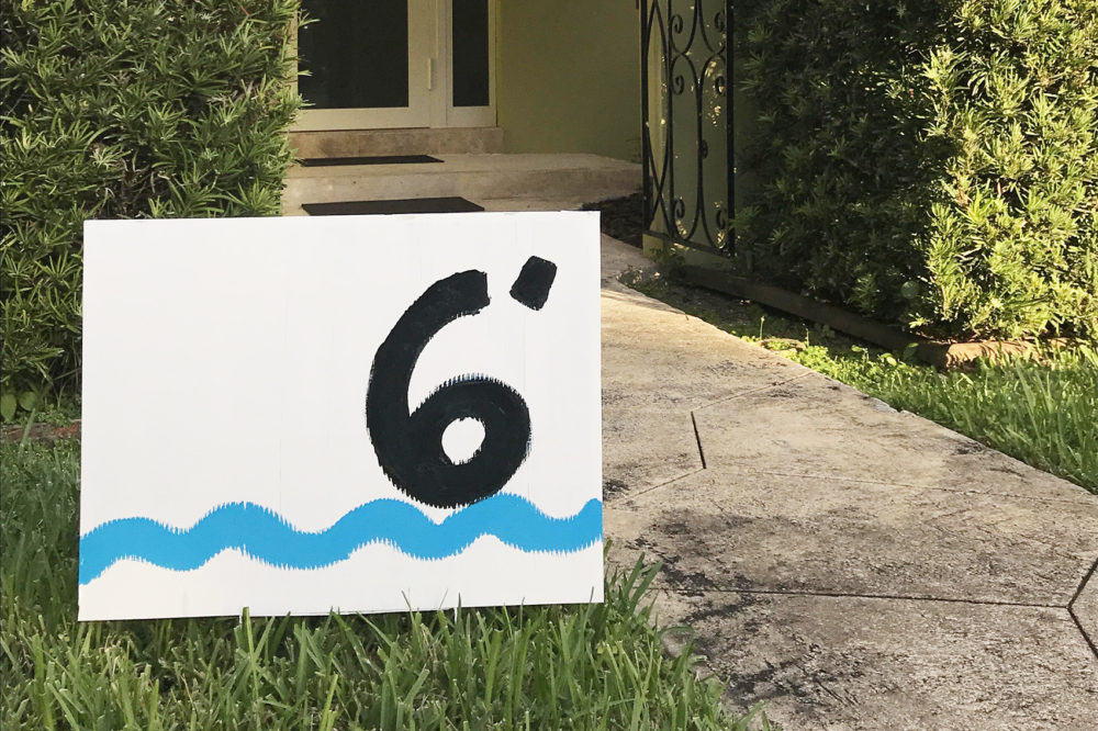 A repurposed campaign sign in front of Xavier Cortada's home, which sits 6 feet above sea level. (Courtesy of Xavier Cortada)