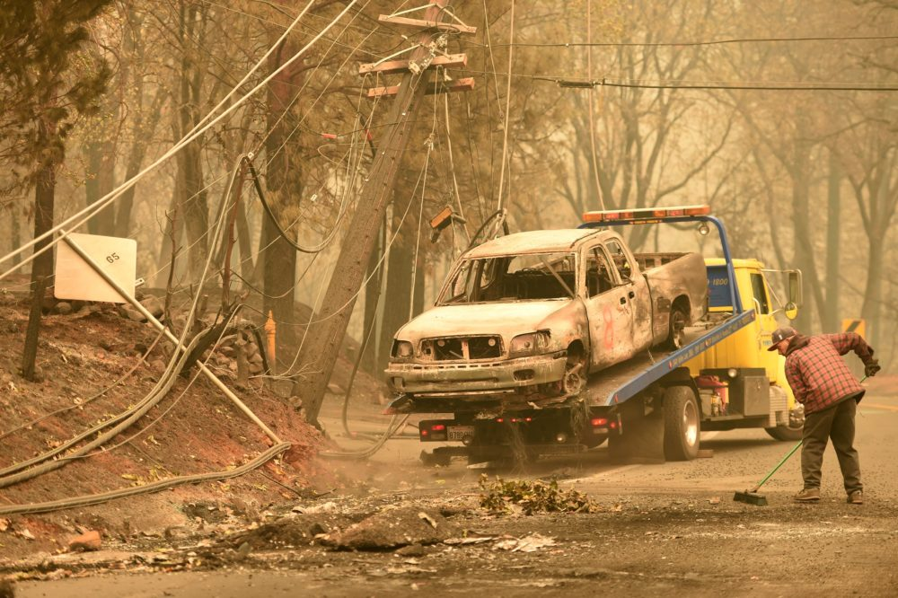 Crews begin removing abandoned vehicles from the streets after the Camp fire tore through the area in Paradise, California on November 12, 2018. - Thousands of firefighters spent a fifth day digging battle lines to contain California's worst ever wildfire as the wind-whipped flames cleaved a merciless path through the state's northern hills, leaving death and devastation in their wake. The Camp Fire -- in the foothills of the Sierra Nevada mountains north of Sacramento -- has killed 29 people, matching the state's deadliest ever brush blaze 85 years ago. More than 200 people are still unaccounted for, according to officials. (Photo by Josh Edelson / AFP)        (Photo credit should read JOSH EDELSON/AFP/Getty Images)