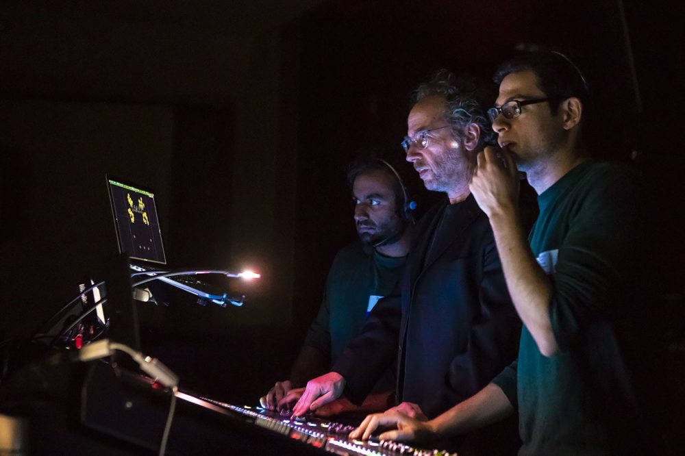 "Composer Tod Machover, center, works the sound board during the dress rehearsal of ""Schoenberg In Hollywood"" along with sound designer Ben Bloomberg, right, and research assistant Nikhi Singh. (Jesse Costa/WBUR)"