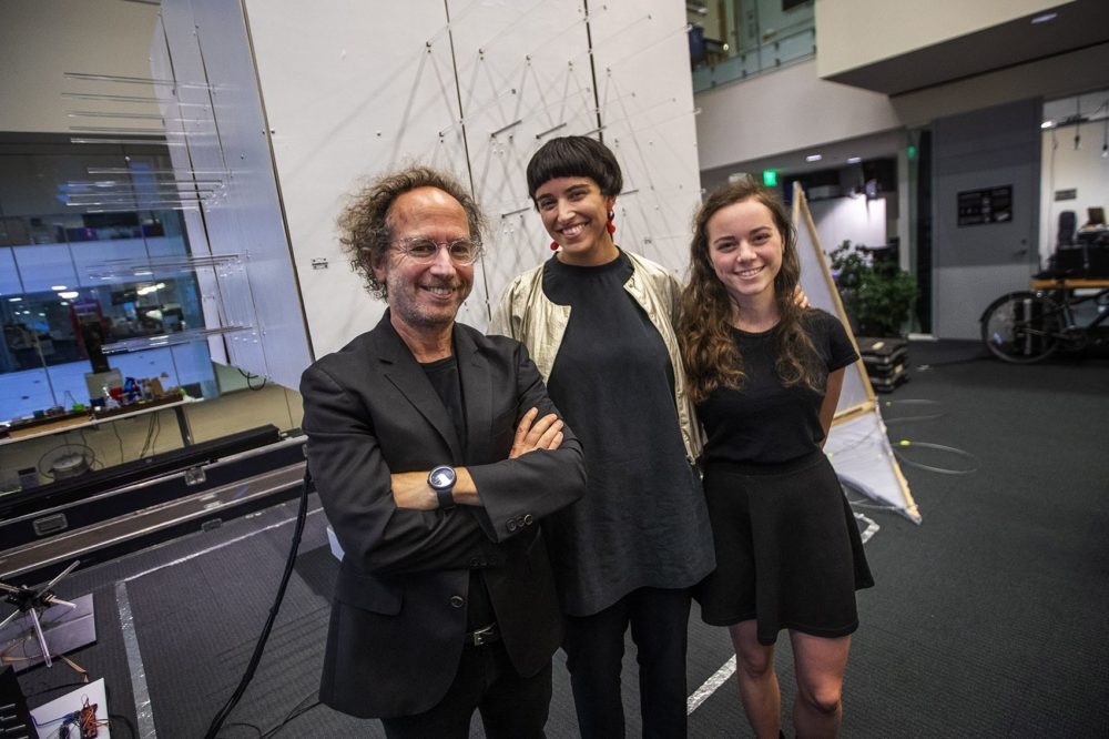 "Tod Machover, director of MIT Media Lab's Opera of the Future group, Nicole L'Huillier and Hannah Lienhard stand in front of ""The Cube,"" a small prototype of a room that changes shape in relation to sound and music being played through it. (Jesse Costa/WBUR)"