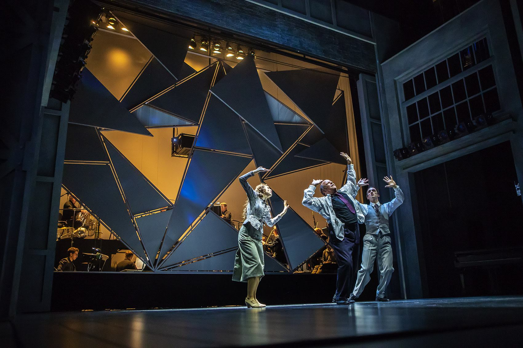 """This fragmenting backdrop, designed by Opera of the Future students comes apart to reveal the orchestra as Sara Womble, Omar Ebrahim and Jesse Darden rehearse the final scene of """"Schoenberg In Hollywood"""" during a dress rehearsal at the Paramount Theater. (Jesse Costa/WBUR)"""