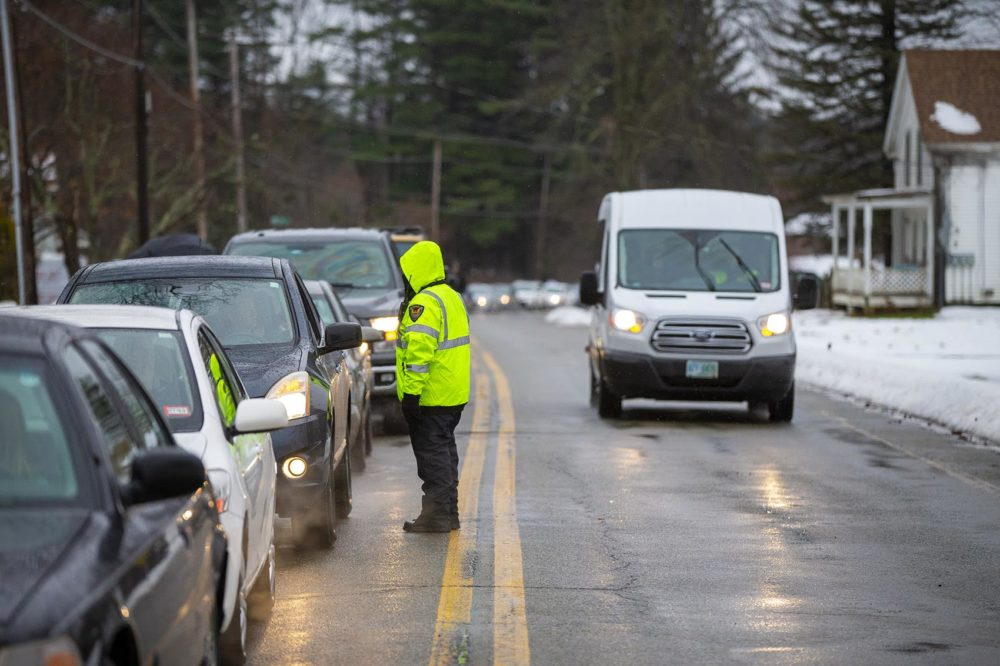 Cars wait on Main Street to park in a lot about a quarter of a mile away from Cultivate. From there customers are shuttled to the facility from the parking lot using vans. (Jesse Costa/WBUR)