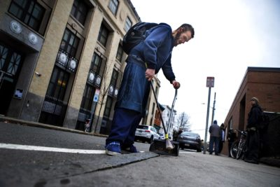 Michael sweeps up cigarettes and other debris from the sidewalk outside a needle exchange in Cambridge. (Jesse Costa/WBUR)