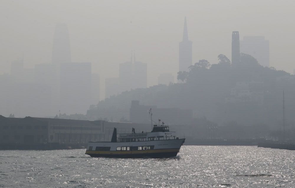 The skyline is obscured by smoke and haze from wildfires as a tour boat makes its way along the waterfront Thursday, Nov. 15, 2018, in San Francisco. Recurring wildfires are sparking concern among medical experts about potentially major health consequences. (Eric Risberg/AP)