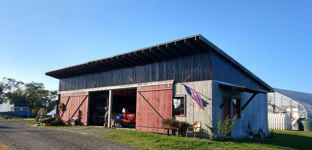 The Jamestown Community Farm's barn was built by local contractors who volunteered their time for the project. To the right, part of the greenhouse is visible along with tanks that store rain water. (Courtesy of Jon Kalish)