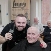 Lenny White smiles with a client during a haircut. (Courtesy)