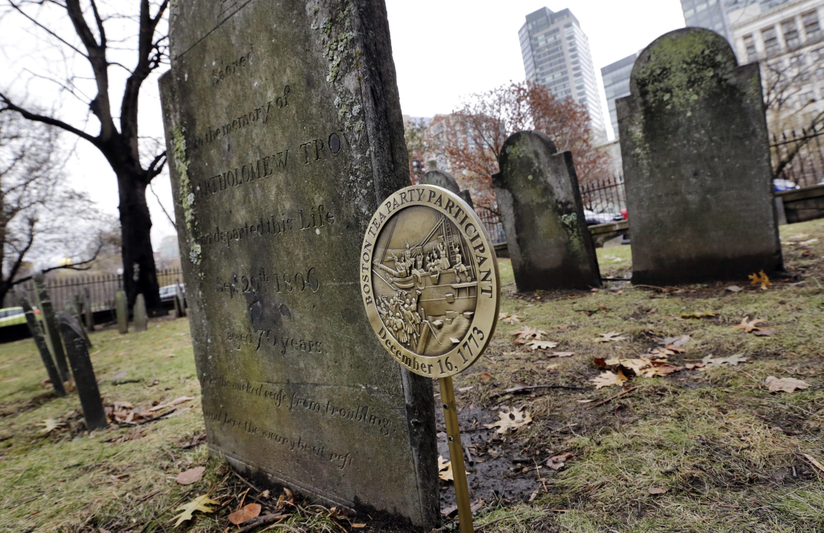 A commemorative marker stands at Central Burying Ground on Boston Common at the gravesite of Bartholomew Trow, a participant of the Boston Tea Party. (Elise Amendola/AP)