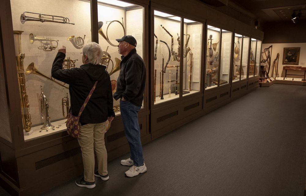 Visitors look at the MFA's collection of rare musical instruments. (Robin Lubbock/WBUR)