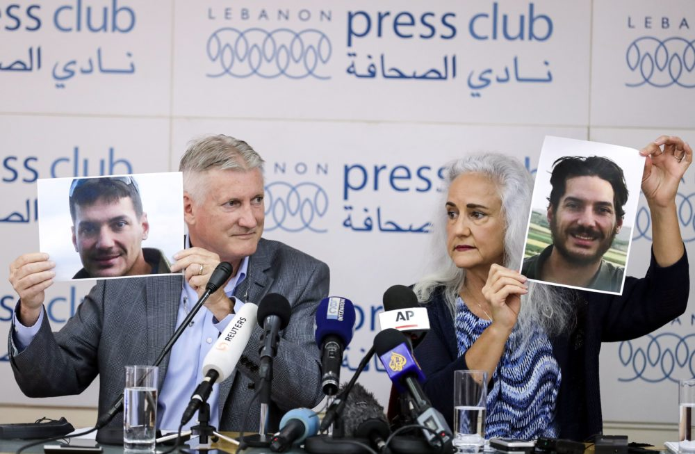 Marc and Debra Tice, parents of American journalist Austin Tice, who was kidnapped in Syria in 2012, hold up photos of their son in Beirut on July 20, 2017. (Joseph Eid/AFP/Getty Images)