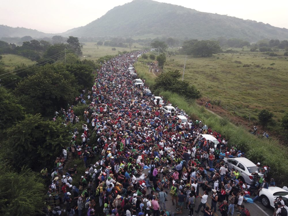 Members of a U.S.-bound migrant caravan stand on a road after federal police briefly blocked their way outside the town of Arriaga in Mexico on Oct. 27. (Rodrigo Abd/AP)