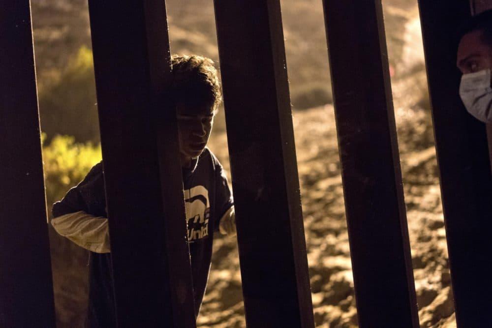 Salvadoran migrant Cesar Jobet, left, talks with fellow migrant Daniel Jeremias Cruz, from the U.S. side of the in Playas de Tijuana, Mexico on Nov. 30. (Ramon Espinosa/AP)