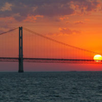 The sun sets over the Mackinac Bridge and the Mackinac Straits as seen from Lake Huron. The bridge is the dividing line between Lake Michigan to the west and Lake Huron to the east. (AP Photo/Al Goldis)