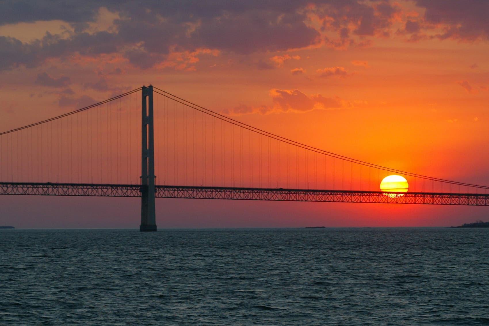 The sun sets over the Mackinac Bridge and the Mackinac Straits as seen from Lake Huron. The bridge is the dividing line between Lake Michigan to the west and Lake Huron to the east. (AP Photo/Al Goldis)