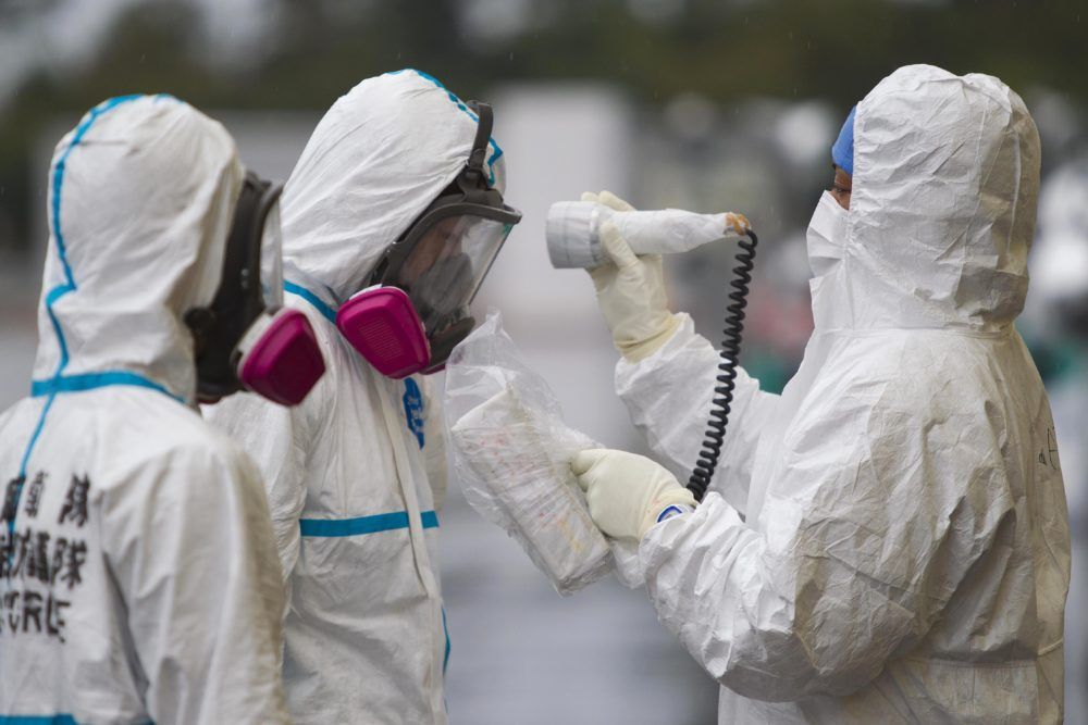 A man is checked for radiation after arriving at a vehicle decontamination center at J-Village, a soccer training complex now serving as an operation base for those battling Japan's nuclear disaster at the tsunami-damaged Fukushima Dai-ichi nuclear plant, in Fukushima prefecture, Japan, Friday, Nov. 11, 2011. (David Guttenfelder/AP)