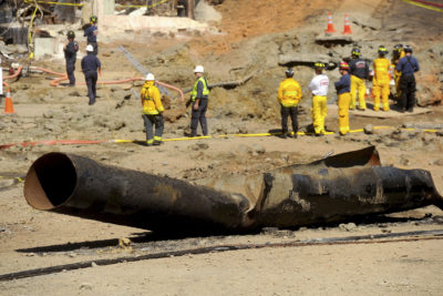 In this Sept. 11, 2010, file photo, a natural gas line lies broken on a San Bruno, Calif., road after a massive explosion. A federal jury found Pacific Gas & Electric Co., California's largest utility, guilty on Tuesday, Aug. 9, 2016, of misleading investigators about how it was identifying high-risk pipelines after the deadly gas line explosion in the San Francisco Bay Area. (AP Photo/Noah Berger, File)