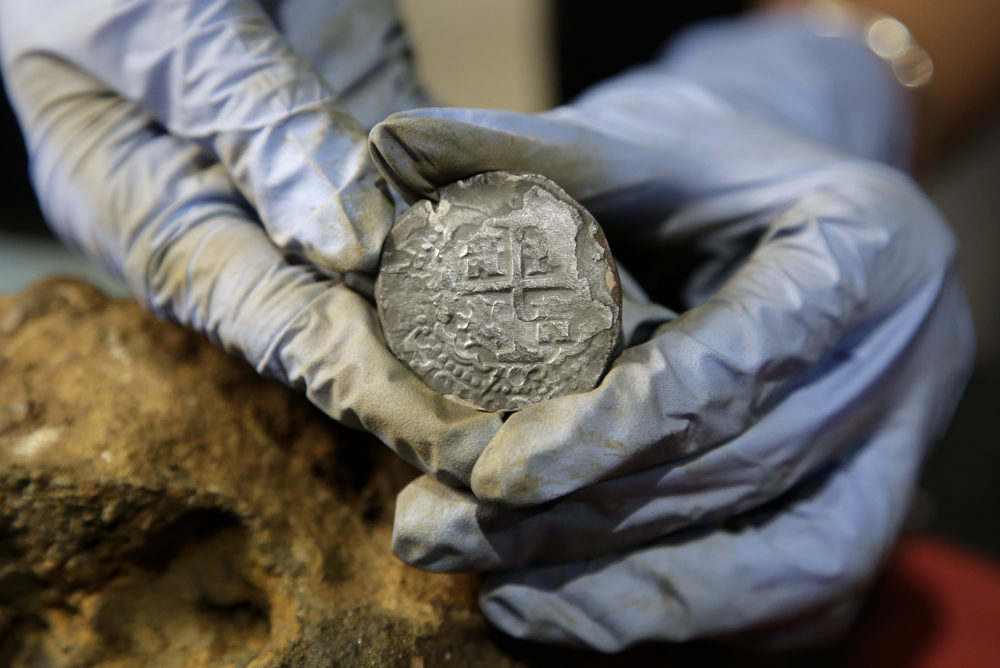 In this Wednesday, Sept. 21, 2016 photo, archaeologist Marie Kesten Zahn, of Yarmouth, Mass. displays a silver coin recovered from the wreckage of the pirate ship Whydah Gally at the Whydah Pirate Museum, in Yarmouth. The undersea explorer Barry Clifford, who discovered the Whydah Gally, the first authenticated pirate shipwreck in U.S. waters, says he's finally found where the ship's vaunted treasure lies after more than 30 years of poking around the murky waters off Cape Cod. (AP Photo/Steven Senne)
