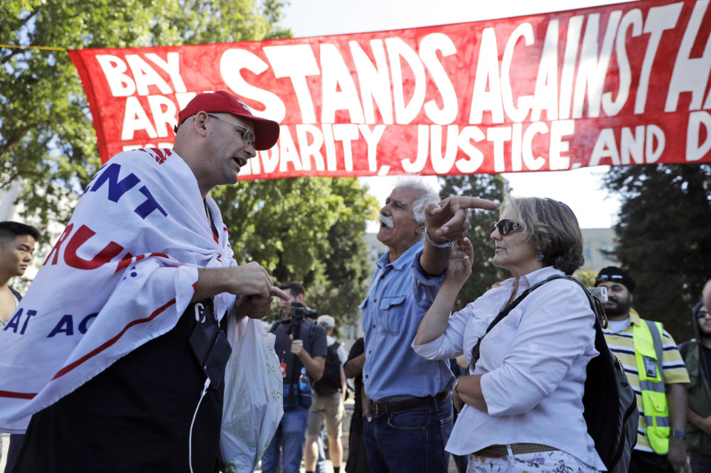 "Donald Trump supporter Arthur Schaper, left, argues his position with Mustafa Payrvand, center, and Christina Tunnah during a free speech rally Sunday, Aug. 27, 2017, in Berkeley, Calif. Protesters gathered for a ""Rally Against Hate"" in response to a planned right-wing protest that raised concerns of clashes and prompted a large police presence. (AP Photo/Marcio Jose Sanchez)"