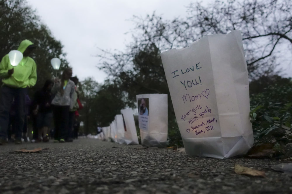Participants pass bags decorated with messages for the deceased during an Out of the Darkness Walk event organized by the Cincinnati Chapter of the American Foundation for Suicide Prevention in Sawyer Point park, Sunday, Oct. 15, 2017, in Cincinnati. (John Minchillo/AP)