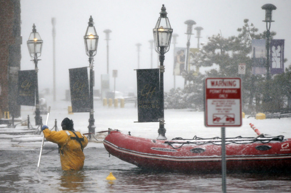 In this Jan. 4, 2018 file photo, a Boston firefighter wades through waters from Boston Harbor that flooded onto Long Wharf in Boston. (Michael Dwyer/AP)