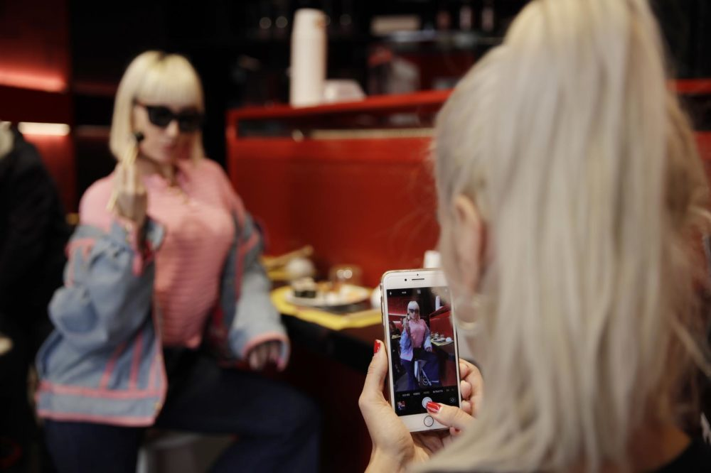"Customer Fashion blogger Clizia Incorvaia, right, takes pictures of her friend singer Vittoria Hyde as they have lunch at the 'This is not a Sushi bar' restaurant, in Milan, Italy, Tuesday, Oct. 16, 2018. Although this is the sixth restaurant the brand ""This is not a sushi bar"" opens in Milan, it has one key difference from its other locations: here payment can be made according to the number of Instagram followers one has, attracting big time social influencers and holders of smaller accounts alike. (AP Photo/Luca Bruno)"