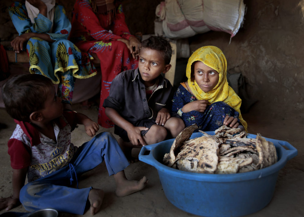 In this Oct. 1, 2018, photo, children sit in front of moldy bread in their shelter, in Aslam, Hajjah, Yemen. In a plastic washtub, the children's mother collects hard bread crumbs even those covered with mold, then mix with water, add salt, and give to her four children. (Hani Mohammed/AP)