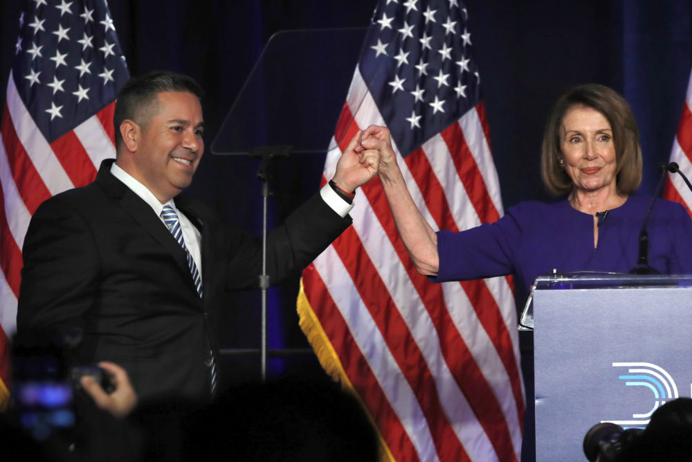 DCCC Chair Ben Ray Luján and House Democratic Leader Nancy Pelosi gesture after speaking to a crowd of volunteers and supporters at an election night event at the Hyatt Regency Hotel, on Tuesday, Nov. 6, 2018, in Washington. (Jacquelyn Martin/AP)