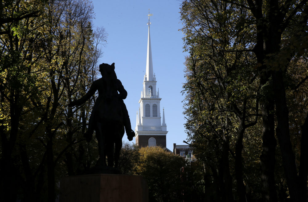 In this Wednesday, Nov. 7, 2018 photo Old North Church stands behind a statue of Paul Revere in the North End neighborhood of Boston. A bronze wreath and plaque that forms part of a memorial, which includes thousands of dog tags honoring soldiers killed in Iraq and Afghanistan, has been installed on the grounds of the church. The new plaque and wreath help explain the meaning of the dog tags and acknowledge Britain's contribution and sacrifice. (Steven Senne/AP)