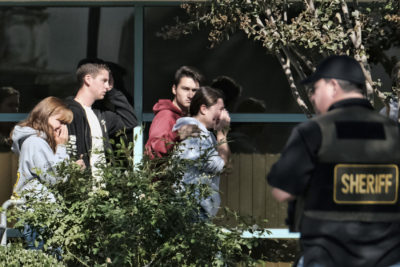 Grieving people are led into the Thousand Oaks Teen Center where families have gathered after a deadly shooting at a bar,  Thursday, Nov. 8, 2018, in Thousand Oaks, Calif. Multiple people were shot and killed late Wednesday by a gunman who opened fire at the Borderline Bar & Grill, which was holding a weekly country music dance night for college students. (AP Photo/Richard Vogel)