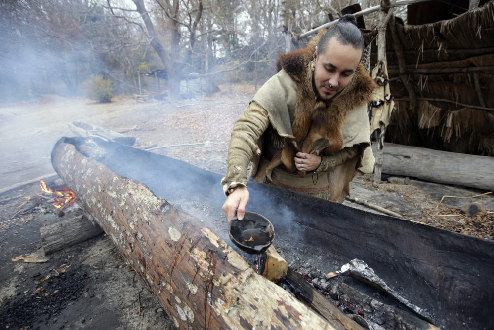 Mashpee Wampanoag Phillip Wynne, of Sagamore, Mass., pours water to control fire and temperatures while making a mishoon, a type of boat, from a tree at the Wampanoag Homesite at Plimoth Plantation, in Plymouth, Mass. Plymouth, where the Pilgrims came ashore in 1620, is gearing up for a 400th birthday, and everyone's invited, especially the native people whose ancestors wound up losing their land and their lives. (AP Photo/Steven Senne)