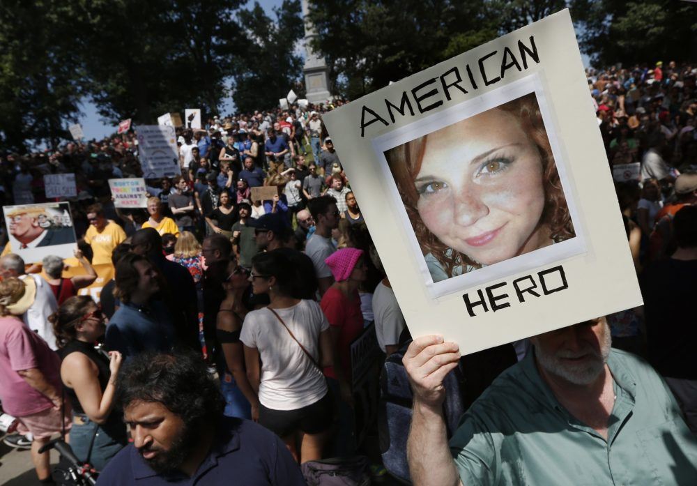 """In this Saturday, Aug. 19, 2017, file photo, a counter-protester holds a photo of Heather Heyer on Boston Common at a """"Free Speech"""" rally organized by conservative activists, in Boston. Heyer was killed when a car, driven by James Alex Fields Jr., plowed into a group of people during protests in Charlottesville, Va. (Michael Dwyer/AP)"""