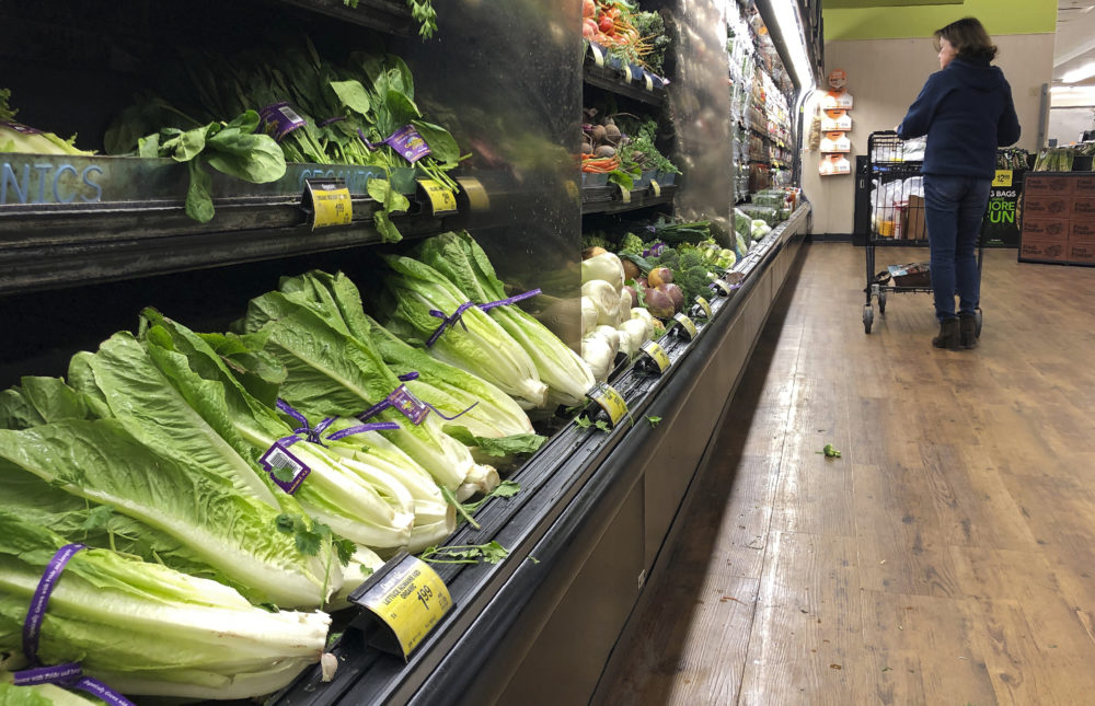 Romaine lettuce still sits on the shelves as a shopper walks through the produce area of an Albertsons market Tuesday, Nov. 20, 2018, in Simi Valley, Calif. (Mark J. Terrill/AP)