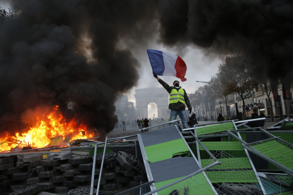 A demonstrator waves the French flag onto a burning barricade on the Champs-Elysees avenue during a demonstration against the rising of the fuel taxes, Saturday, Nov. 24, 2018 in Paris. French police fired tear gas and water cannons to disperse demonstrators in Paris Saturday, as thousands gathered in the capital and staged road blockades across the nation to vent anger against rising fuel taxes and Emmanuel Macron's presidency. (Michel Euler/AP)