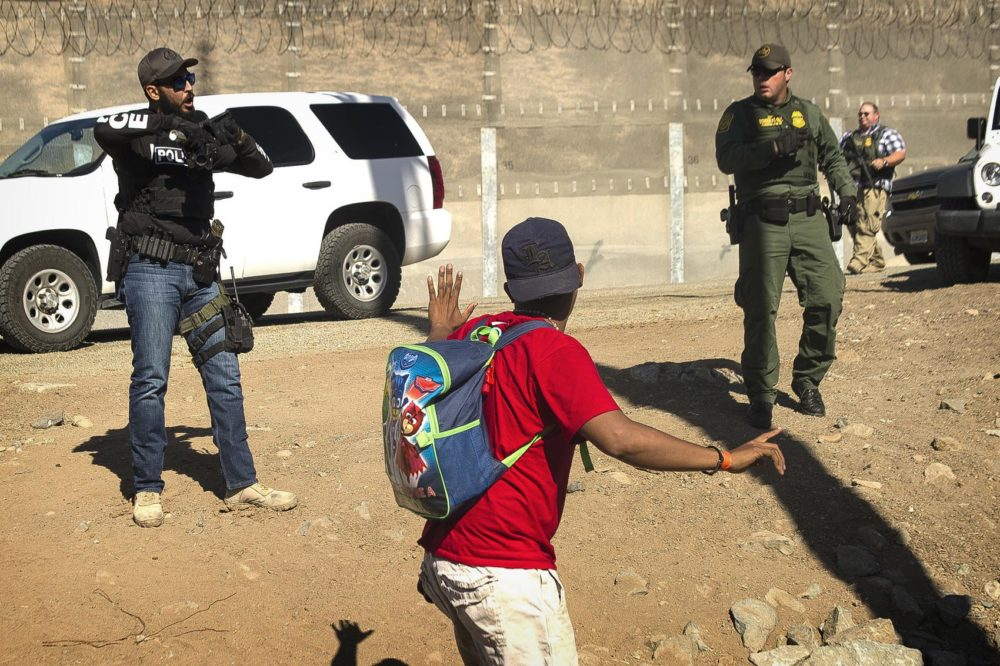 A Central American migrant is stopped by U.S. agents who order him to go back to the Mexican side of the border, after a group of migrants got past Mexican police at the Chaparral crossing in Tijuana, Mexico, Sunday, Nov. 25, 2018, at the border with San Ysidro, California. The mayor of Tijuana has declared a humanitarian crisis in his border city and says that he has asked the United Nations for aid to deal with the approximately 5,000 Central American migrants who have arrived in the city. (AP Photo/Pedro Acosta-APTOPIX)