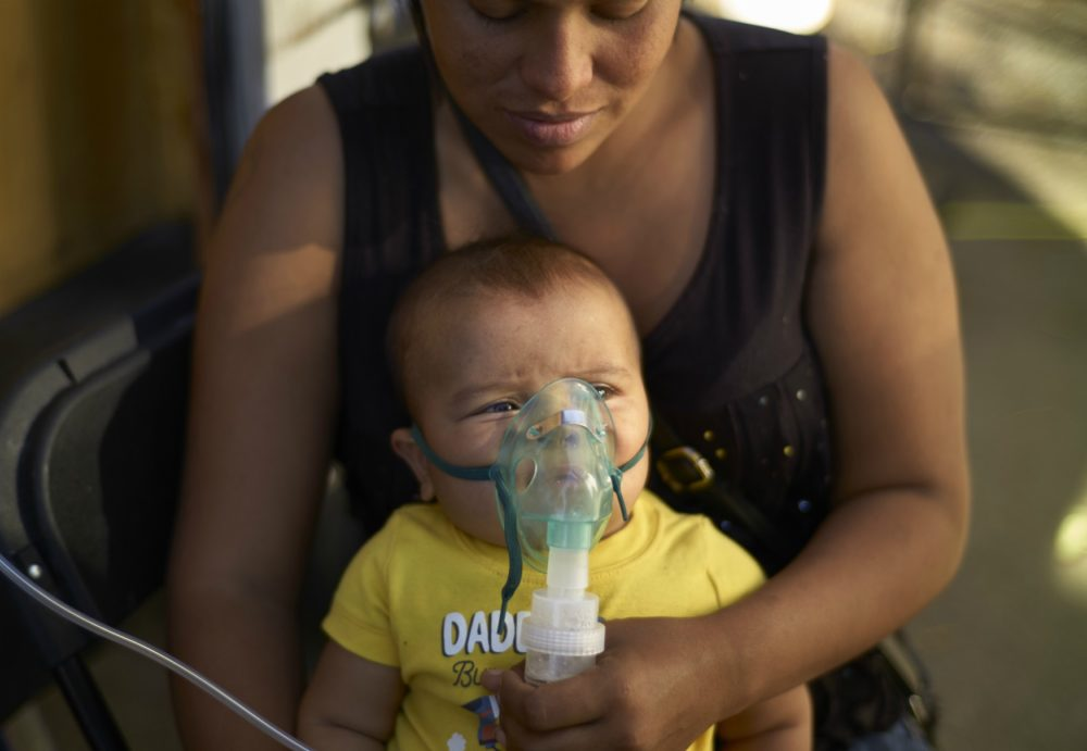 Honduran migrant Janet Zuniga holds her 5-month-old son Linder, as he receives medical treatment outside a shelter, Monday, Nov. 26, 2018, in Tijuana, Mexico. A day after a march by members of the migrant caravan turned into an attempt to breach the U.S. border with Mexico, many migrants appeared sullen, wondering whether the unrest had spoiled whatever possibilities they might have had for making asylum cases. (Gregory Bull/AP)