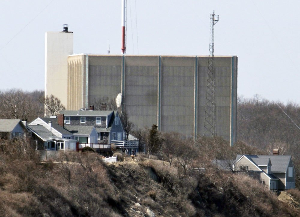 In this March 30, 2011 file photo, a portion of the Pilgrim Nuclear Power Station is visible beyond houses along the coast of Cape Cod Bay in Plymouth, Mass. (Steven Senne/AP)