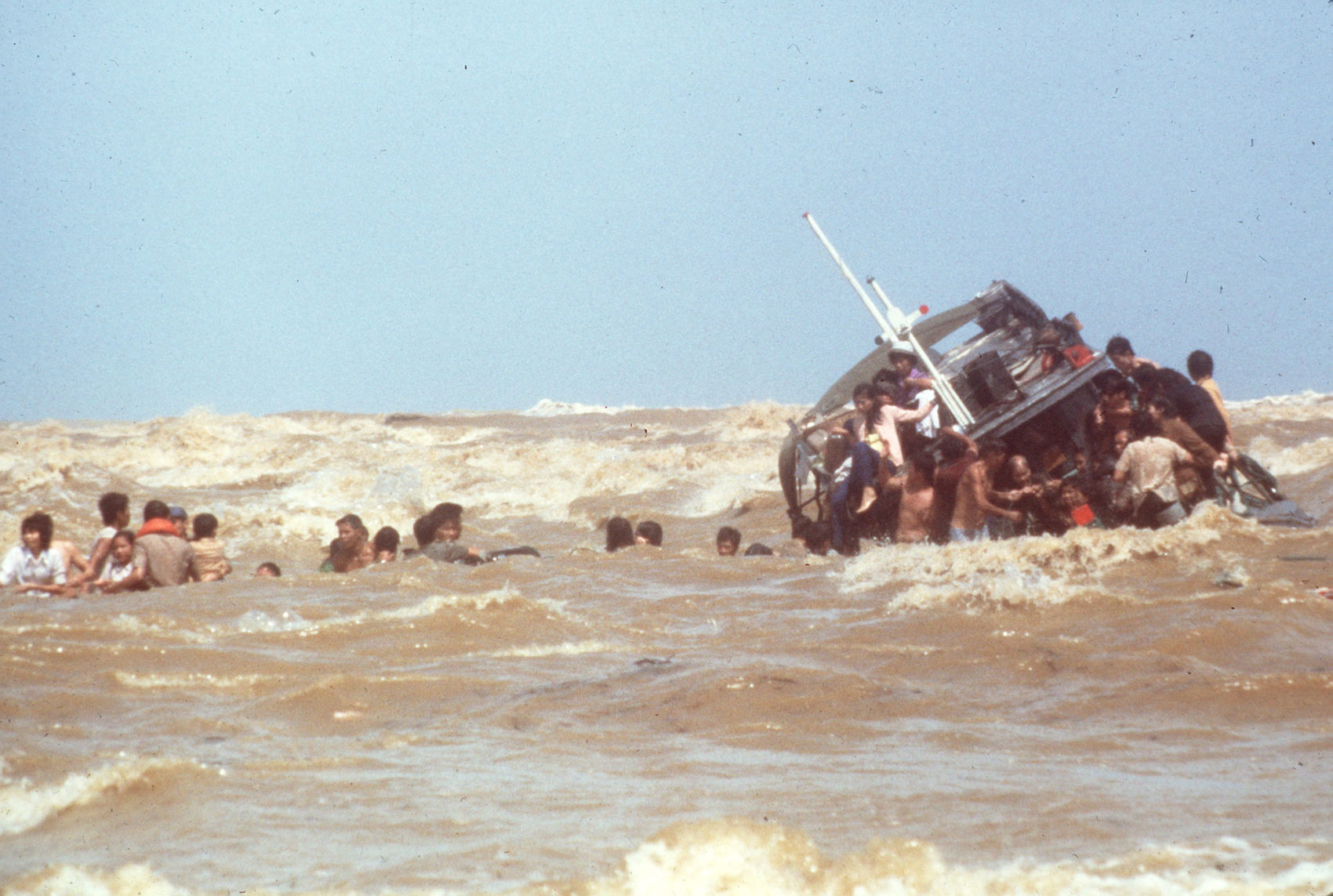 Vietnamese refugees scramble from a sinking boat which they beached at Kuala Trengganu, Malaysia, in December 1978. (AP)