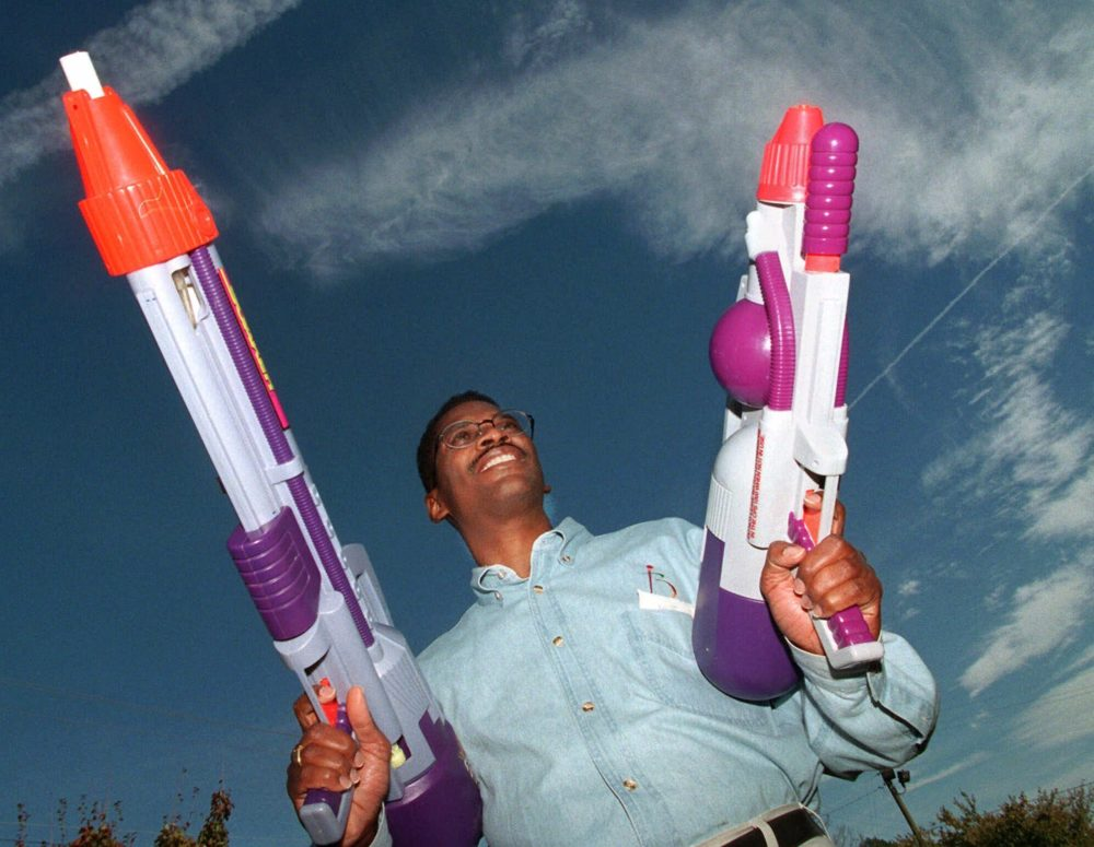 """Toy inventor Lonnie Johnson poses with his creation """"The Super Soaker"""" outside his Marietta, Ga., office  Nov. 12, 1998.  Johnson, who once worked for NASA, hit on his idea for the high-powered water gun while trying to invent a heat pump that would use water instead of Freon.  (John Bazemore/AP)"""