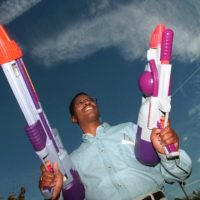 "Toy inventor Lonnie Johnson poses with his creation ""The Super Soaker"" outside his Marietta, Ga., office  Nov. 12, 1998.  Johnson, who once worked for NASA, hit on his idea for the high-powered water gun while trying to invent a heat pump that would use water instead of Freon.  (John Bazemore/AP)"